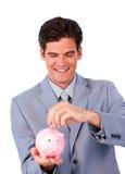 Ассерторические деньги сбережени бизнесмена в piggy-банке стоковые изображения