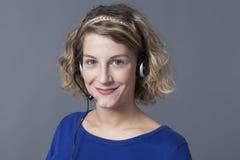 Ассерторические молодые белокурые женские нося наушники стоковое изображение rf
