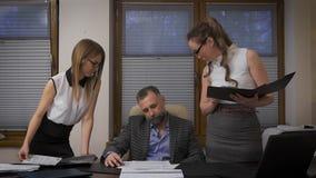 2 ассистента женщин, который нужно примениться для подписи к его боссу Респектабельный бизнесмен с серыми волосами в своем твердо акции видеоматериалы