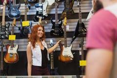 Ассистентская показывая гитара клиента на магазине музыки Стоковые Фотографии RF