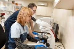 Ассистенты лаборатории анализируют образец смотря через микроскоп Сделайте исследование в лаборатории Наука и концепция медицины стоковые фотографии rf