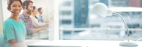 Ассистенты обслуживания клиента с шлемофонами с яркой предпосылкой офиса Стоковые Фотографии RF
