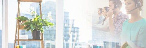 Ассистенты обслуживания клиента с шлемофонами с яркой предпосылкой офиса Стоковое Фото