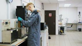 Ассистент лаборатории взгляда со стороны в маске кладет цилиндр в прибор акции видеоматериалы