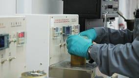 Ассистент лаборатории взгляда со стороны кладет цилиндр в рассматривает прибор сток-видео