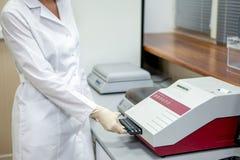 Ассистент лаборатории нагружает образцы в прибор для анализа, взгляда со стороны стоковая фотография rf