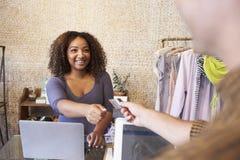 Ассистент на магазине одежды принимая кредитную карточку от клиента Стоковое фото RF