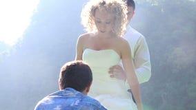 Ассистент помогает платью невесты правильному в шлюпке сток-видео