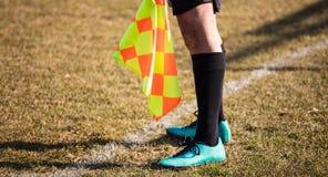 Ассистент рефери футбола стоит на боковой линии с флагом на руках Предпосылка поля нерезкости зеленая, конец вверх Стоковые Фото