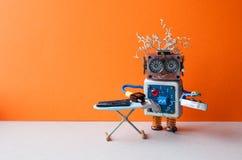 Ассистент робота домашний утюжа черные брюки с утюгом пара на доске Интерьер комнаты пола оранжевой стены серый творческо стоковые фото