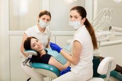 Ассистент whit доктора обрабатывая зубы пациента, предотвращая костоеду r стоковые фото