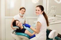 Ассистент whit доктора обрабатывая зубы пациента, предотвращая костоеду r стоковое изображение rf