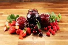 Ассортимент варениь, сезонных ягод, вишни, мяты и плодов в стеклянном опарнике стоковые изображения rf
