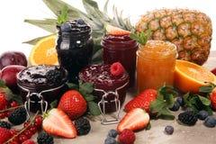 Ассортимент варениь, сезонных ягод, слив, мяты и плодов в стеклянном опарнике стоковые изображения rf