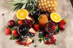 Ассортимент варениь, сезонных ягод, слив, мяты и плодов в стеклянном опарнике стоковое фото rf
