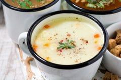 Ассортимент горячих супов в кружках, крупный план Стоковые Изображения