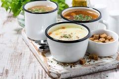 Ассортимент горячих супов в кружках на деревянной доске Стоковое фото RF