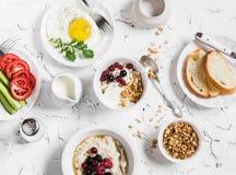 Ассортимент завтрака - творога с югуртом и ягодами, овсяной кашей с медом и ягодами, яичницей, свежими овощами, ho Стоковые Изображения RF
