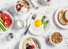 Ассортимент завтрака - яичницы, свежих овощей, овсяной каши с ягодами, творога, югурта и ягод, домодельного granola Стоковые Изображения RF
