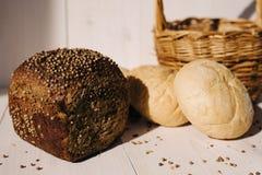 Ассортимент испеченного хлеба на белой предпосылке деревянного стола, трудном свете стоковая фотография