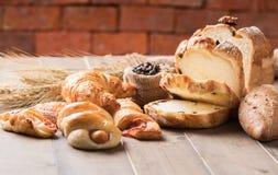 Ассортимент испеченных хлеба и пшеницы на деревянной таблице стоковая фотография rf