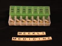 Ассортимент пилюлек в зеленой и белой еженедельной коробке пилюльки с еженедельной медициной сказал по буквам в плитках на черной Стоковые Фотографии RF
