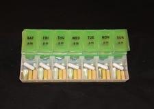 Ассортимент пилюлек в зеленой и белой еженедельной коробке пилюльки на черной предпосылке Стоковые Фотографии RF