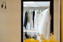 Ассортимент платьев вися на вешалке на студии стоковые фото