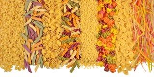 Ассортимент покрашенных сырых итальянских макаронных изделий на белизне Стоковое Изображение