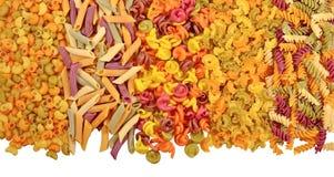 Ассортимент покрашенных сырых итальянских макаронных изделий на белизне Стоковое Фото