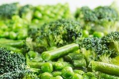 Ассортимент свежих, который замерли зеленых горохов, французская фасоль, брокколи с крупным планом изморози как предпосылка Стоковое фото RF