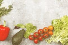 Ассортимент свежих овощей перчит, томаты вишни, авокадо, шпинат, петрушка на светлой предпосылке Взгляд сверху, космос экземпляра Стоковые Фото