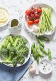 Ассортимент свежих овощей сада - спаржа, брокколи, фасоли, томаты, чеснок, зеленые горохи на светлой предпосылке, взгляд сверху Стоковые Фотографии RF