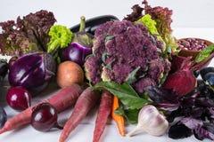 Ассортимент свежих сырцовых фиолетовых доморощенных овощей на белой таблице Стоковые Изображения