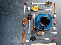 Ассортимент сухого чая и чашка горячего чая Зеленый чай, черный чай, зеленый чай, rooibos, сушит розовые бутоны в ложках Стоковые Изображения
