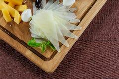 Ассортимент сыра на предпосылке деревенской разделочной доски деревянной Стоковое Изображение