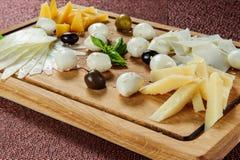 Ассортимент сыра на предпосылке деревенской разделочной доски деревянной Стоковое Изображение RF