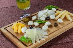 Ассортимент сыра на предпосылке деревенской разделочной доски деревянной Стоковая Фотография RF