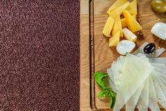Ассортимент сыра на предпосылке деревенской разделочной доски деревянной Стоковое фото RF