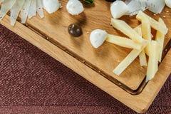 Ассортимент сыра на предпосылке деревенской разделочной доски деревянной Стоковая Фотография