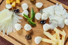 Ассортимент сыра на предпосылке деревенской разделочной доски деревянной Стоковое Фото