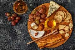 Ассортимент сыра с вином, медом, гайками и виноградиной на cutti стоковая фотография rf
