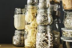 Ассортимент сырых зерен, хлопьев и макаронных изделий в стеклянных опарниках на деревянном столе r стоковая фотография rf