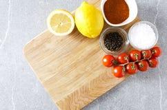 Ассортимент трав, лимонов и томатов на разделочной доске Подготовка для варить еду в кухне стоковые изображения rf