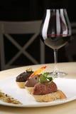 Ассортимент хлеба канапе pate на белой плите с стеклянным красным вином, темной предпосылкой Стоковые Изображения