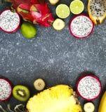 Ассортимент экзотических плодоовощей на серой каменной предпосылке с экземпляром s Стоковое Изображение