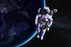 Астронавт в космическом пространстве на предпосылке земли ночи стоковые изображения