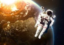 Астронавт в космическом пространстве против фона  Стоковые Изображения