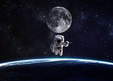 Астронавт в космическом пространстве против фона  Стоковые Фото