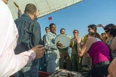 Асуан, Египет 17-ое февраля 2017: Партия западных туристов в типичной шлюпке Нила вызвала Felucca, с египетский играть стоковое фото rf
